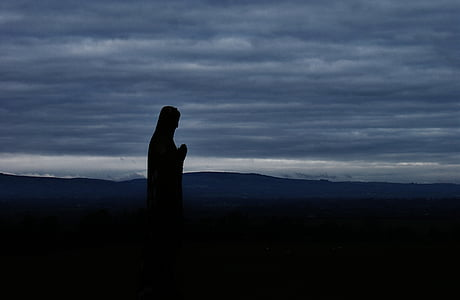 silhouette of statue near hill at dawn