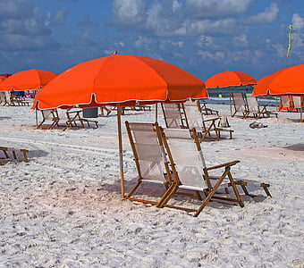 deck hairs and umbrellas at the beach during day
