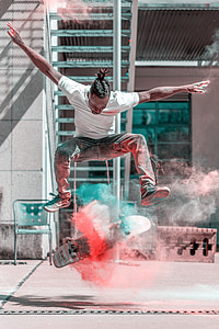 man doing flip trick with skateboard and smoke