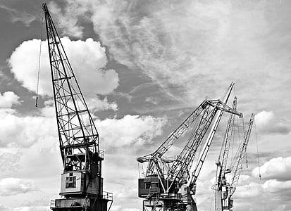 grayscale photography of industrial cranes
