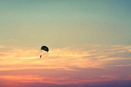 silhouette of person with parachute