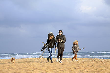 three persons walking on seashore at daytime