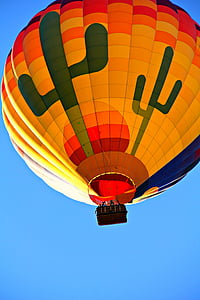 photo of yellow, red, and blue hot-air balloon in flight