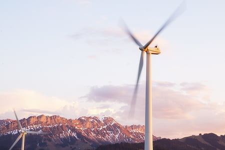 spinning windmill under white sky at daytime