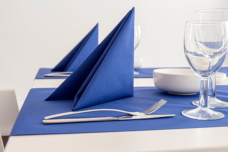 blue table napkin near silver fork and knife on top of blue textile