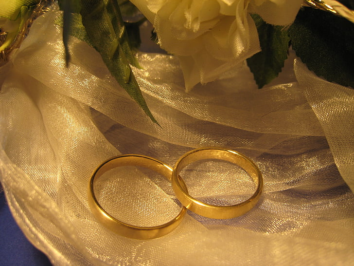 two gold-colored rings on white textile