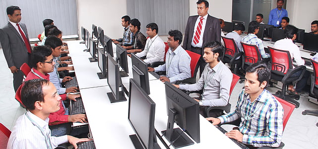 group of men sitting in front of table facing monitors