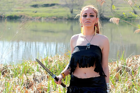 woman in black tube top and black skirt holding sword