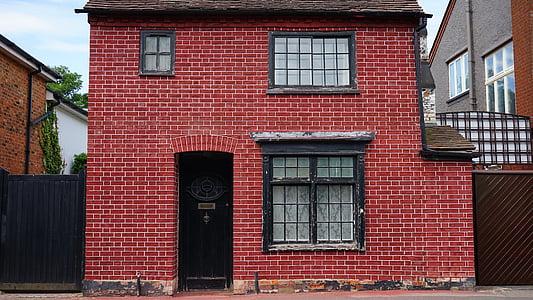 2-storey red brick house during daytime
