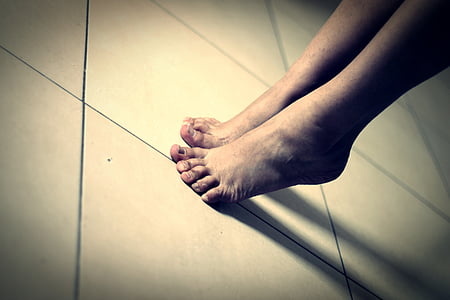 person's feet on white ceramic tiles