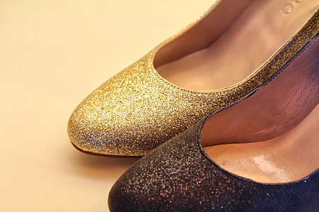 unpaired women's gold and black glittered shoes