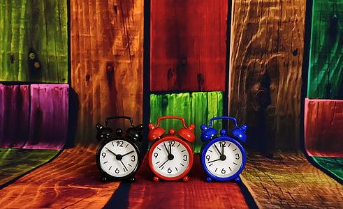 three black, red, and blue dual-bell alarm clocks