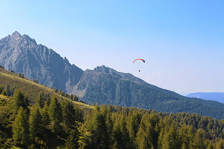 person parachuting down hillside with pine trees under blue sky during daytime
