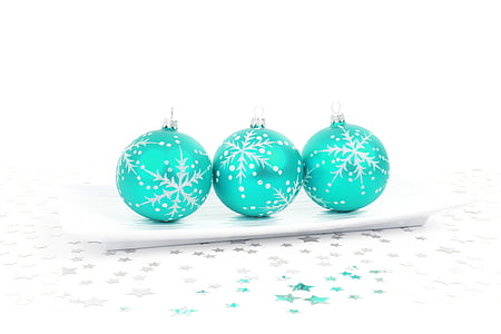 three teal Christmas baubles on white ceramic plate