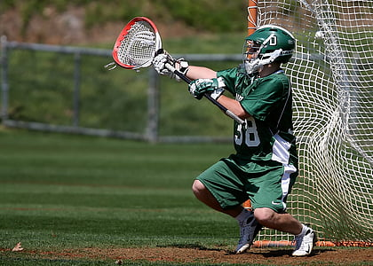 player in green jersey and shorts holding lacrosse stick