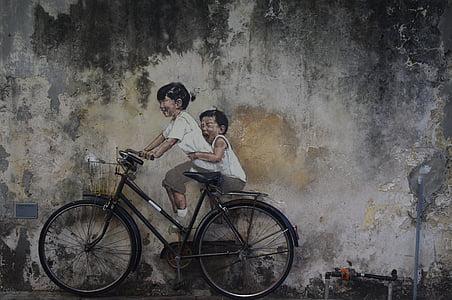 two children riding black city bike