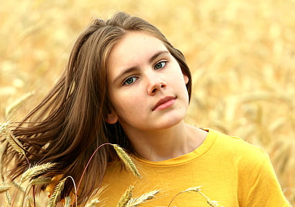 woman in yellow crew-neck shirt surrounded by yellow petaled flowers