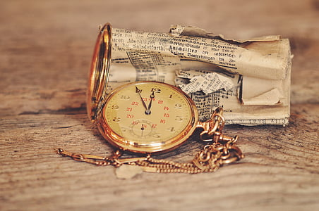 round gold-colored analog pocket watch at 11:55