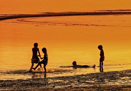 silhouette of four children on seashore during golden hour