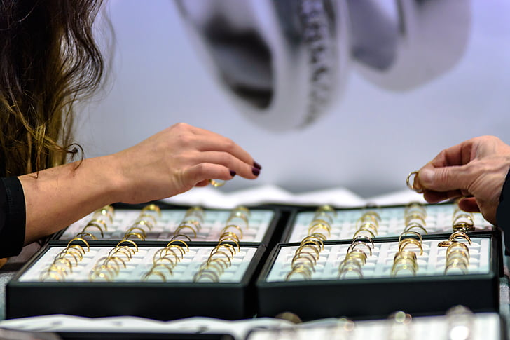 woman choosing from gold-colored ring lot