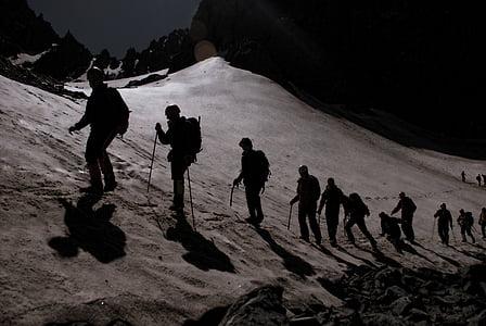 silhouette of people walking on desert