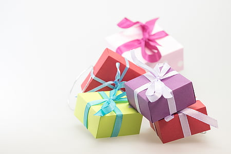 shallow focus photography of four assorted-color gift boxes