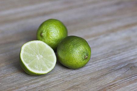 three green calamundin fruits on brown surface