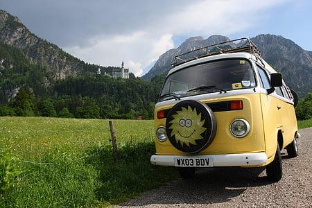 yellow Volkswagen Kombi parked beside grass field
