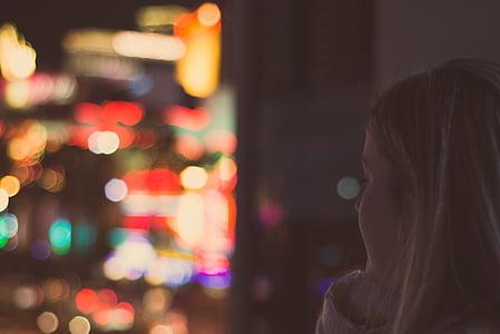 woman in white top in city light bokeh