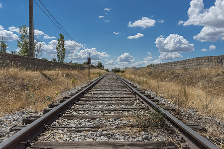 black and gray railway between brown grasses under clear blue sky during daytime