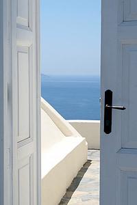 slightly open white door overlooking body of water