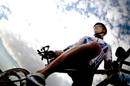 man in white and blue sport gear riding on bicycle