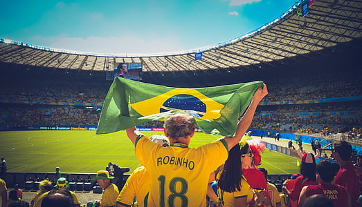 photo of man raising flag of Brazil on sports stadium
