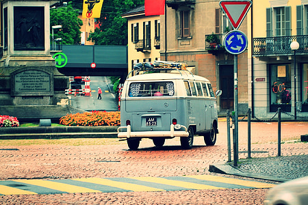 white and blue Volkswagen T2 on road in front of beige concrete 2-storey house