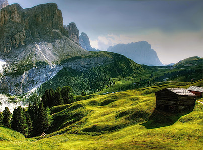 landscape photo of shack on hill near mountains