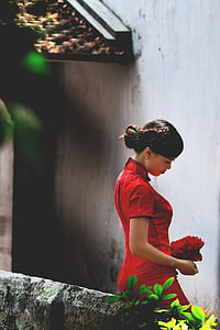 woman wearing red Chinese dress standing and leaning on gray surface