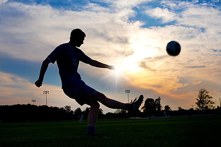 silhouette photography of man kicking ball