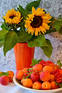 sunflowers with orange vase beside tray of peach and red berries fruits