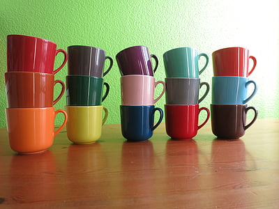 assorted-color ceramic mugs on brown wooden table
