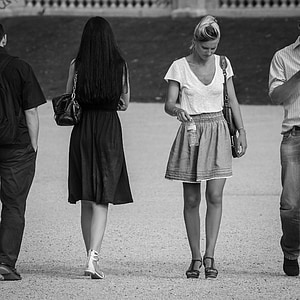 two men and women walking opposite way grayscale photography