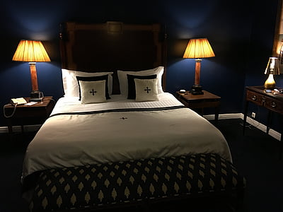 person taking photo of bedroom with table lamp turned on