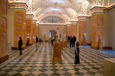 people standing and walking inside museum with statuettes