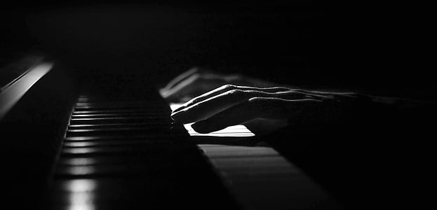 grayscale photography of person playing piano