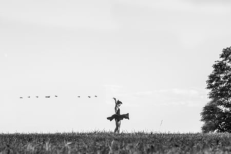 grayscale photo of woman dancing on lawn