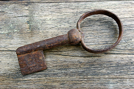 rusted brown skeleton key on brown wooden board
