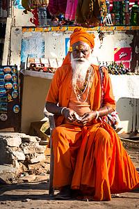 men's orange monk dress sitting on chair