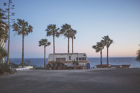 gray camper trailer near the ocean
