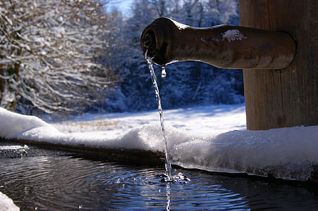 brown bamboo faucet dropping water near trees covered with snow at winter