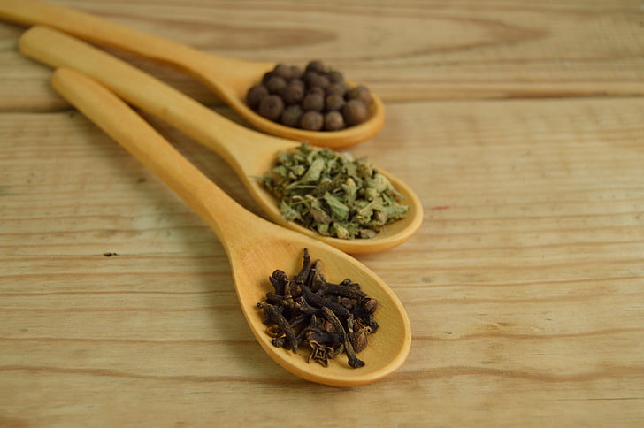 brown wooden ladles filled with herbs and spices
