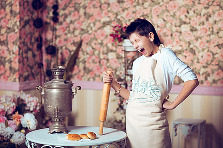 woman holding brown wooden rolling pni